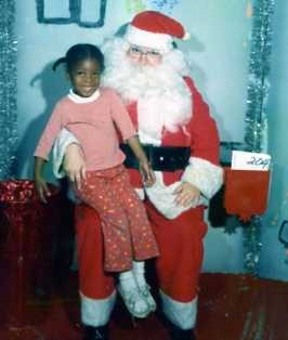 African american girl sitting on santa's lap
