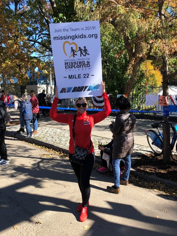 woman in red holding sign for marathon