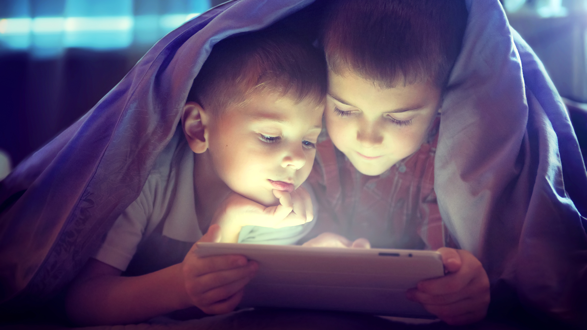 Kids reading under a blanket